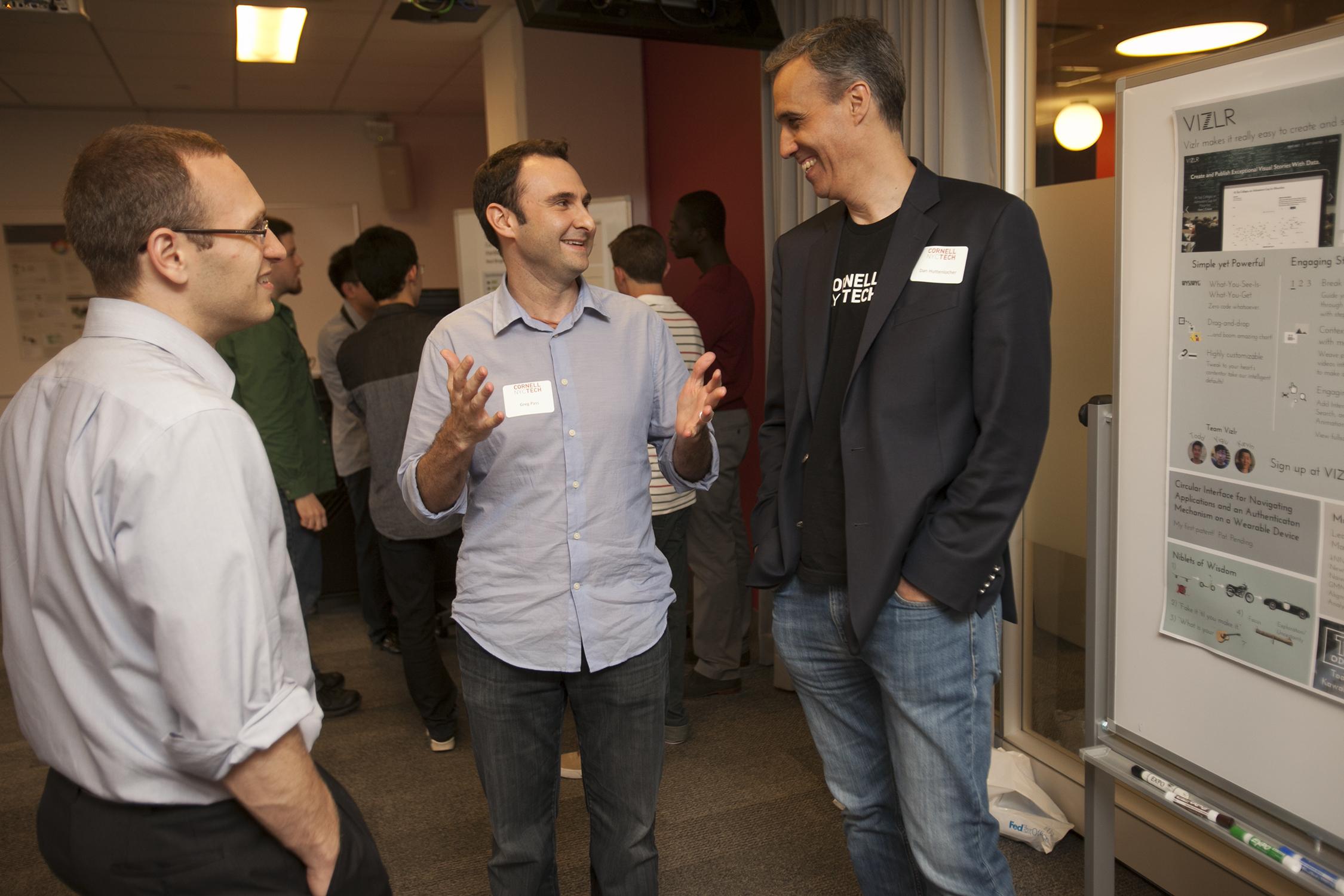 3 men smiling while having a conversation