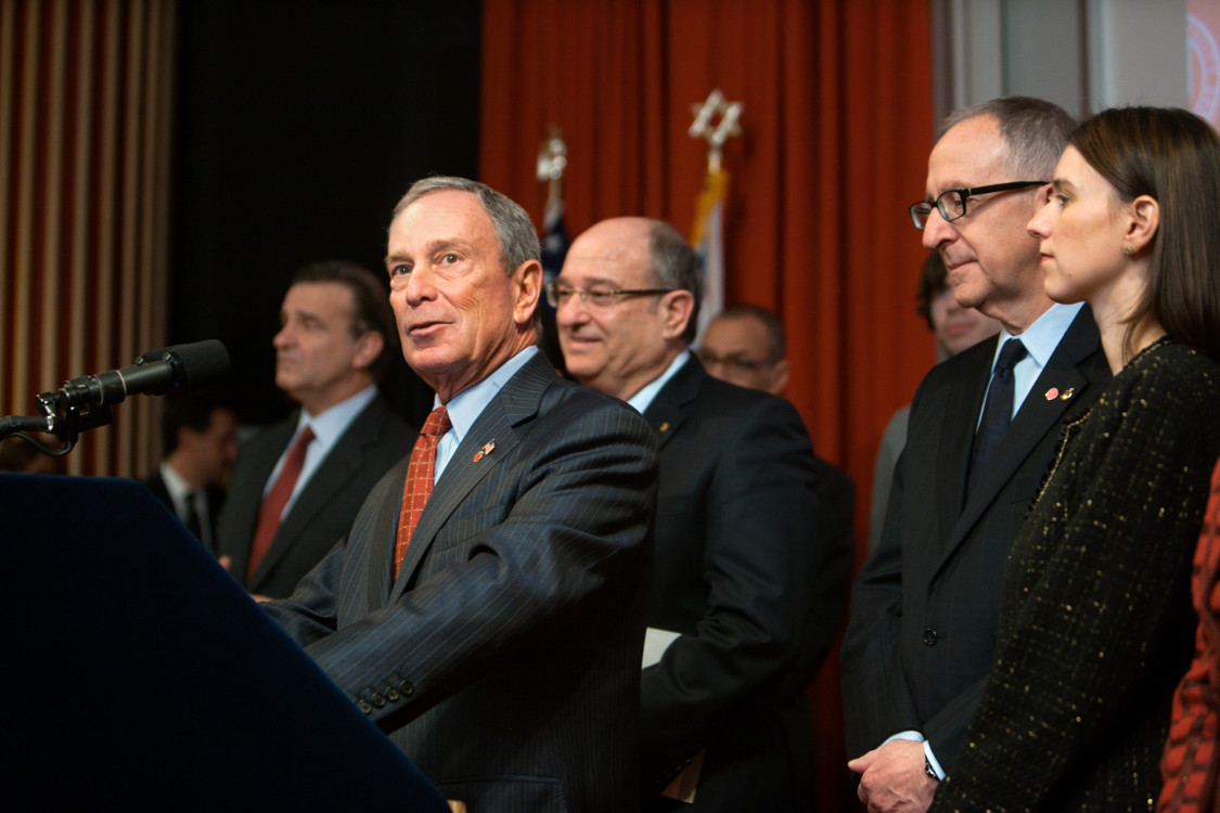 Michael Bloomberg speaking from a podium