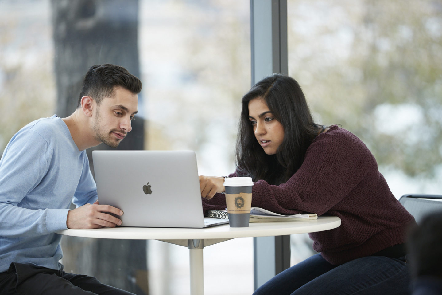 Two students collaborating on a laptop