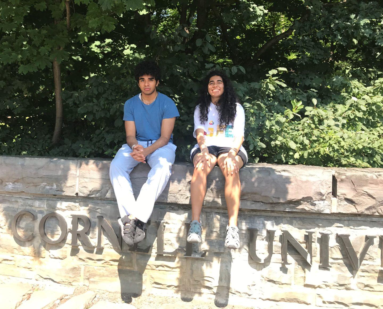 Eeshan and Vini Tripathii sitting on a wall at Cornell University.